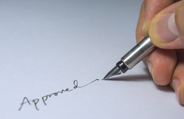 Closeup of approved signature with fingers and pen, light bulb from left side in the dark room